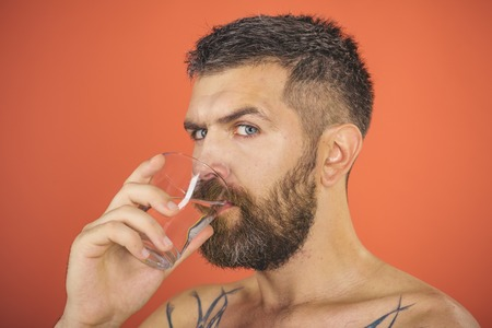 Man with beard on face drink water from glass on red background, healthcare and life source, hangover and thirst, refreshing Imagens - 90305585