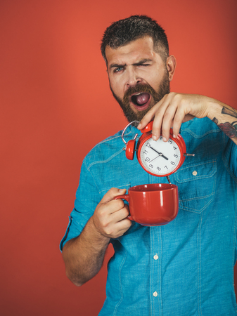 man with beard on sleepy face with morning coffee cup and alarm clock on red background, copy space