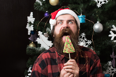 Winter holiday and xmas. Christmas man with beard on happy face and lollipop. santa claus man in hat at decoration. New year guy lick candy or sweet. Party celebration and blowjob.