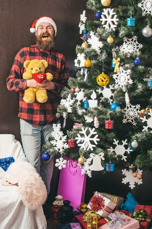 Christmas man with beard on happy face hold bear. New year guy in hat at Christmas tree. Winter holiday and xmas. Santa claus man with present and decoration. Party and celebration.