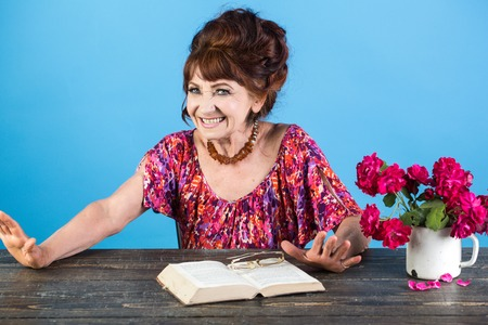 Pension and retirement, old age. Old woman reading book with glasses at flowers. Writer and poet, granny read fairytale. happy old lady or grandmother. Teacher or professor, education, teachers day. Imagens