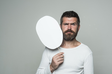 Guy or bearded man on grey background. Hipster with serious face hold paper nameplate. Feeling and emotions. Barber fashion and beauty. Man with long beard and mustache., copy space