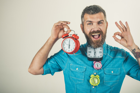 Lifetime, business and deadline. Overtime and urgency. happy man with beard hold alarm clock show ok gesture. Time and perfect morning. Time management and countdown, watchmaker