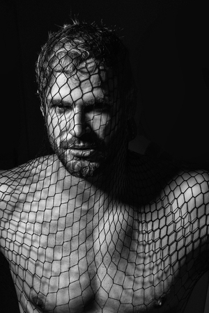 Young handsome man bearded guy with beard or robber bandit gangster wears mask of black fishnet stocking on face on dark background with bare muscular chest Stock Photo - 90215671