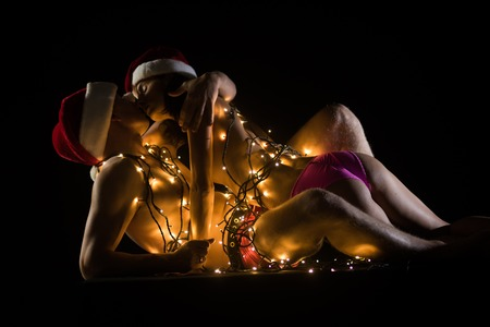 Relations of couple in illuminated garland. Santa man and girl with naked body. New year boyfriend and girlfriend isolated on black. Christmas couple in love of sexy man and woman. Love and sex games.