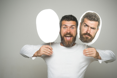 Guy or bearded man on grey background. Hipster with sad and happy face hold portrait nameplate. Feeling and emotions. Barber fashion and beauty. Man with long beard and mustache., copy space