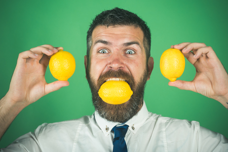 Fruit and healthy organic food. happy man with long beard eat lemon. Dieting and fitness. Vitamin citrus at hipster on green background. Vegetarian, health and wellbeing.