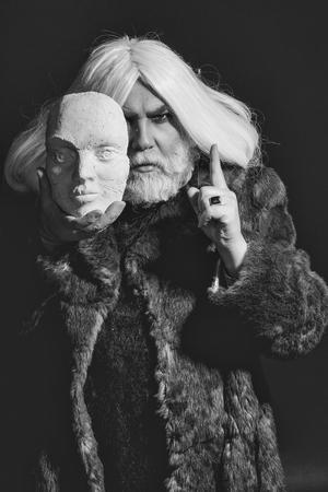 黒い背景にリングで白い彫刻の頭を持つ毛皮のコートで深刻な顔と髪に長いひげを持つ古いドルイドひげの男 写真素材