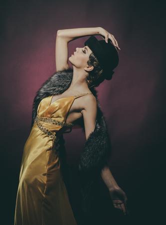 Kijk en retro-stijl, pin-up. Meisje in modieuze gele jurk, hoed en bont. Schoonheid en vintage mode. Pin-up mooie fashion model pose op Bourgondische achtergrond. Vrouw met retro haar en make-up. Stockfoto