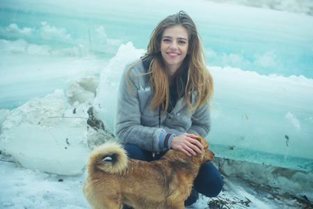 new year of dog. woman with happy face and dog at cracked frozen ice block in cold winter weather, christmas holiday and vacation.
