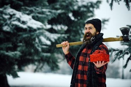 겨울 휴가 축하. 크리스마스 방황, 하이킹, 여행. 나무에 도끼와 크리스마스 hipster 등심입니다. 선물 상자가 눈 감기 숲에 새 해 남자. 도끼와 겨울 숲에