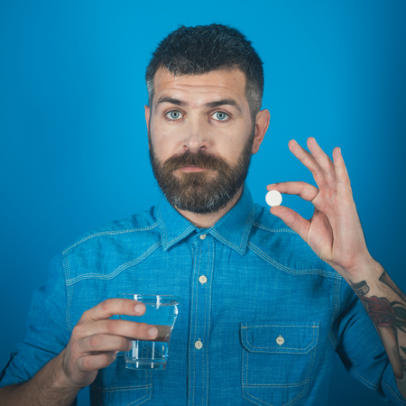 Man with beard hold water glass on blue background, headache. Hipster drink pill with water, illness. painkiller drug and antidepressant. Health and medicine, flu and cold. Treatment, hypnotic tablet. Фото со стока