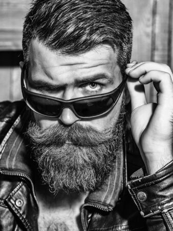 Frown bearded man hipster brutal male with beard and moustache in leather jacket looks above sunglasses on wooden background Reklamní fotografie
