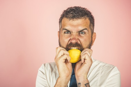 Vegetarian, health and wellbeing. angry man with long beard eat lemon. Dieting and fitness. Vitamin citrus at hipster on pink background. Fruit and healthy organic food, copy space Stok Fotoğraf