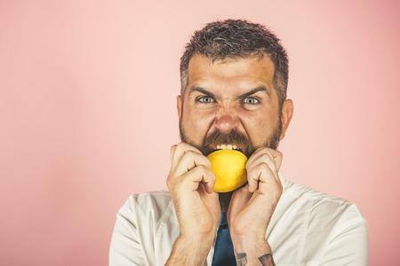 Vegetarisch, gezondheid en welzijn. boze man met lange baard eet citroen. Dieet en fitness. Vitamine citrus op hipster op roze achtergrond. Fruit en gezonde natuurvoeding, kopie ruimte