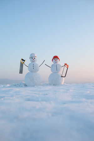 Building and repair work. New year snowman from snow with saw. Snowman builder in winter in helmet. Happy holiday and celebration. Christmas or xmas decoration.