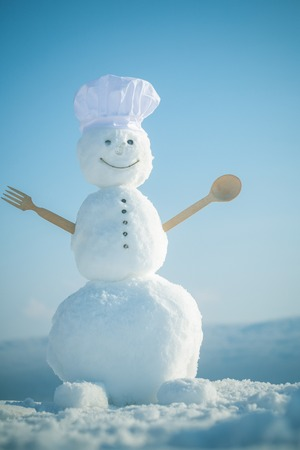 Xmas or christmas cooking. Snowman chef in winter with kitchen spoon. Christmas food cooking. Happy holiday celebration. New year snowman in cook hat. Banco de Imagens