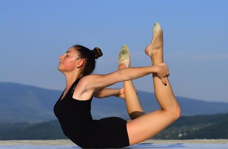 pilates training van meisje op blauwe hemelachtergrond. Gymnastiekschool en energie. Sport en succes. Flexibiliteit in acrobatiek en fitnessgezondheid. De vrouwenturner in zwarte sportkleding in yoga stelt.