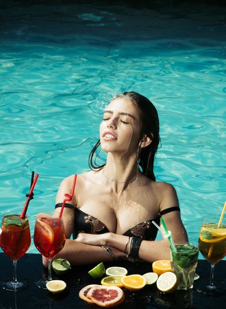 Summer vacation and party. Drink, food and happiness. Woman with alcoholic beverage and fruit. Swimming and relax in water pool. Cocktail and sexy girl in pool.