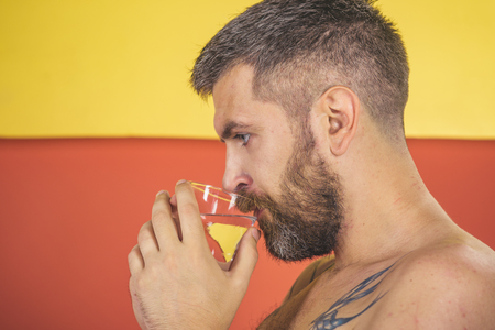 Health and dieting. Hipster drink clean healthy water, refreshing. Hangover and thirst. Life source and healthcare. Man with long beard hold water glass on colorful background.