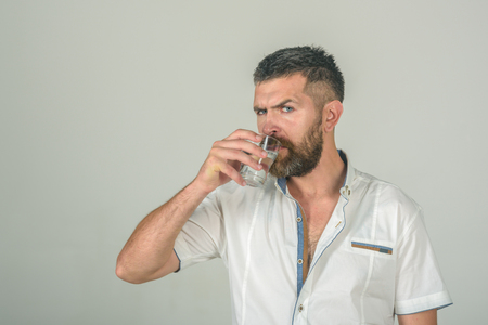 Life source and healthcare. Health and dieting. Man with long beard hold water glass on grey background. Hangover and thirst. Hipster drink clean healthy water, refreshing. Imagens - 90215679