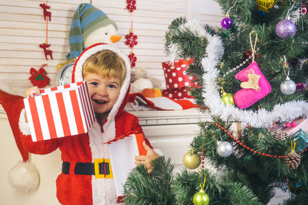 New year small boy at decoration toy. Winter holiday and vacation. Christmas happy child with gift box, boxing day. Santa claus kid decorating Christmas tree.. Xmas party celebration. Stock Photo