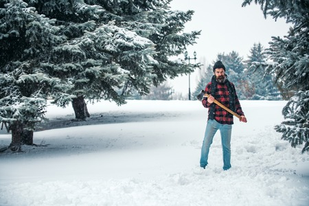 Christmas hipster lumberjack with ax in wood.. Man with beard in winter forest with snow hold axe. New year man in snowy cold forest. Wanderlust, hiking and travel. Winter holiday and celebration. Banco de Imagens