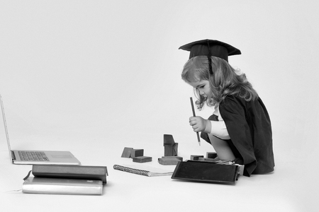 Little boy child in graduation squared cap and black mantle sitting and drawing by pencil in copy book near box with colored pencils wooden blocks diaries and open notebook isolated Imagens - 90217729