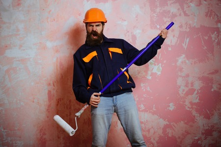 Guy with repair roller on pink background. Working and repair. Builder man in helmet with tool. Man with long beard on shouting face in hard hat. Building and construction.