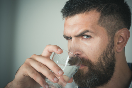 man with beard on serious face drink water from glass on grey background, healthcare and life source, hangover and thirst, refreshing, copy space Imagens - 90499137