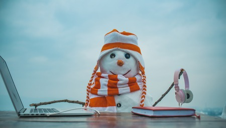 Snowman in winter with laptop, headset and book. Xmas or christmas decoration, audio book. New year snowman in hat. Happy holiday celebration, new technology. Christmas and education, fairytale. Stock Photo