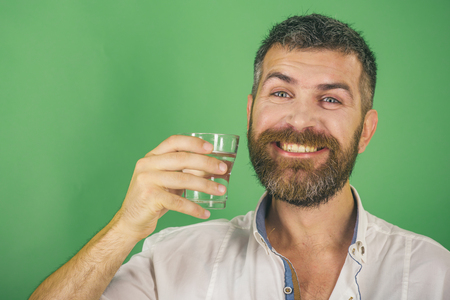Hangover and thirst. Health and dieting. Man with long beard hold water glass on green background. Life source and healthcare. Happy hipster drink clean healthy water, refreshing, copy space