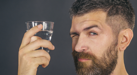 Life source and healthcare. Hangover and thirst. Hipster drink clean healthy water, refreshing. Health and dieting. Man with long beard hold water glass on grey background. Imagens - 90943130