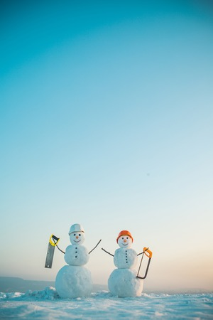 Christmas or xmas decoration. Snowman builder in winter in helmet. Happy holiday and celebration. New year snowman from snow with saw. Building and repair work. Stock Photo