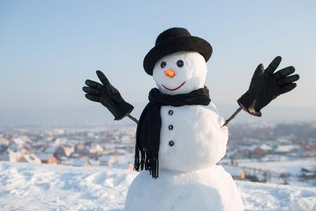 Snowman gentleman in winter black hat, scarf and gloves.