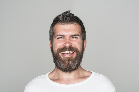 Man with long beard and mustache. Guy or bearded man on grey background. Barber fashion and beauty. Feeling and emotions. Hipster with happy face.