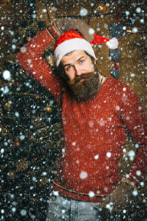 christmas new year snow concept Santa claus man on wooden background. Winter holiday and xmas. Boxing day and party celebration. Christmas man with beard on happy face. New year guy at Christmas tree