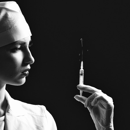 Young doctor with beautiful face in medical uniform holding syringe with liquid on black background