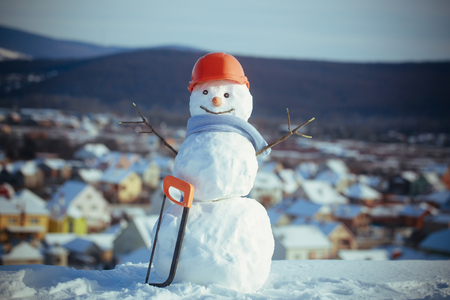 Snowman builder in winter in helmet. Christmas or xmas decoration. Happy holiday and celebration. New year snowman from snow with saw. Building and repair work.