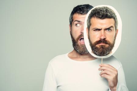 驚きと深刻な顔を持つヒップスターは、肖像画のネームプレートを保持します。長いあごひげと口ひげを持つ男。感情と感情灰色の背景に男やあご