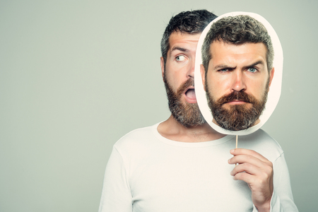 Hipster with surprised and serious face hold portrait nameplate. Man with long beard and mustache. Feeling and emotions. Guy or bearded man on grey background. Barber fashion and beauty., copy space