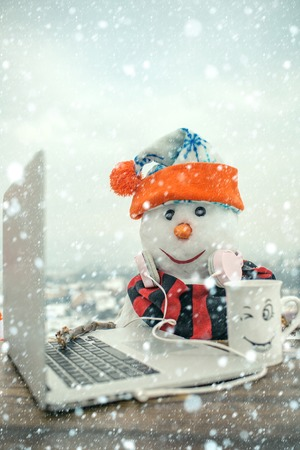 new year christmas snow concept Christmas and hot wine.. Happy holiday celebration, new technology. Xmas or christmas decoration, audio book. Snowman in winter with laptop, headset and tea cup.