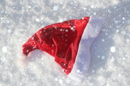 new year christmas snow concept Santa claus cap on snowy background. Santa red hat on snow. Christmas and new year. Winter white landscape. xmas holidays celebration concept.