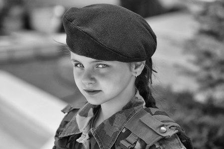 Young girl child soldier with serious pretty face brunette in army camouflage black beret on head on natural background outdoor