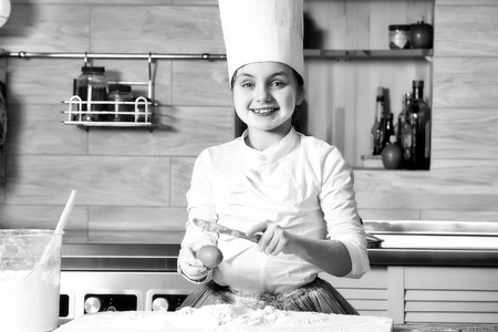 Cooking, food, study. Small girl cooking with flour in chef hat.  Stock Photo