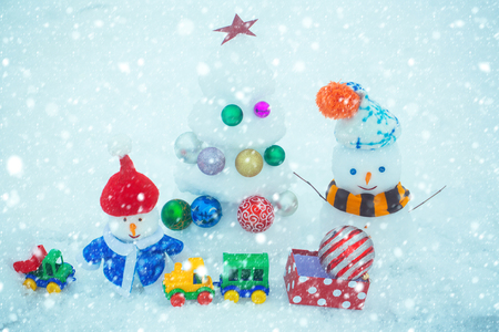 new year christmas snow concept Snow sculptures on white background. Christmas tree with balls, present box, toy train and car. Winter holidays concept. xmas and new year. Snowmen with smiley Stock Photo