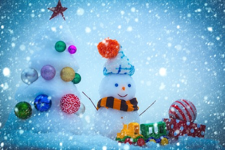 new year christmas snow concept Snowman with smiley face in hat and scarf. Snow sculptures on blue background. xmas and new year. Christmas tree with ball decorations, toy train and present box. Stock Photo