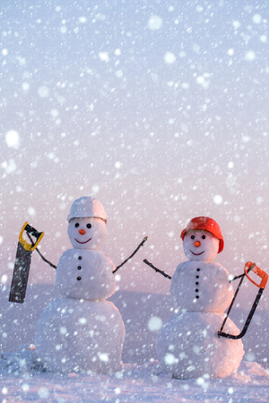 new year christmas snow concept Christmas or xmas decoration. Snowman builder in winter in helmet. Building and repair work. Happy holiday and celebration. New year snowman from snow with saw.