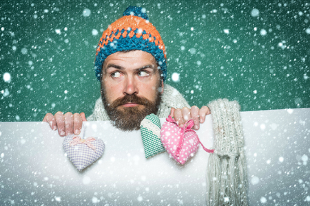 new year christmas snow concept Guy with sad face in winter hat and scarf. Hipster with heart on green white background. Holiday celebration and party. Valentines day and love. Man with long beard