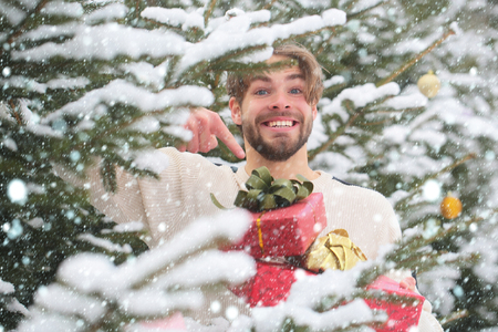 new year christmas snow concept Man pointing finger at red boxes in snow wood. Holidays celebration concept. Season greetings and xmas gifts. Macho smiling with presents on winter day. Stock Photo